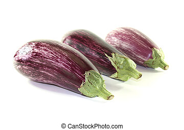 Eggplants - three fresh purple eggplant on a white...