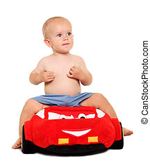 Little boy in a red soft toy car