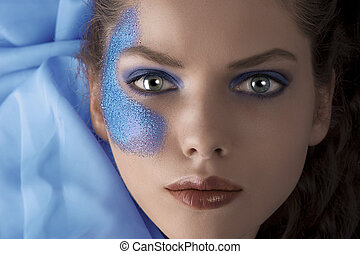 face shot of a laying model with blue glitter make up