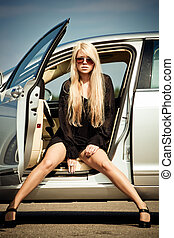 Car and babeYoung sexy blond girl sitting in a luxury car