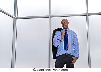 Relaxed businessman beside a big office window