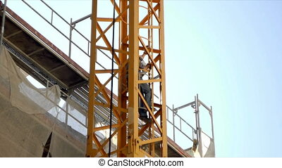 Crane Climb - Man climbs ladder of construction crane