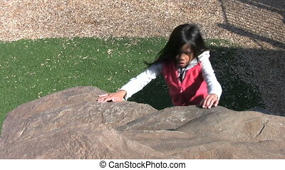 Girl Rock Climbing At Playground - A cute determined Asian...
