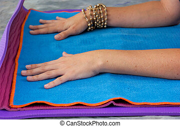 womans hands on yoga mat - Womans hands are placed on yoga...