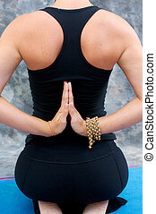 young woman in yoga Virasana or hero pose with reverse...