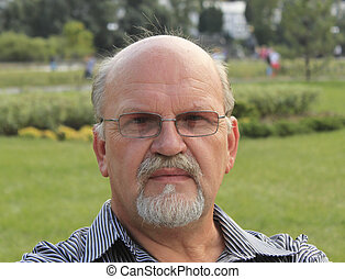 Pensive bald mature man with a beard, close-up outdoors