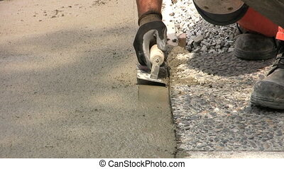 Finishing A Sidewalk - A construction worker finishes...
