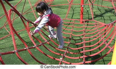Girl Climbing Web At Playground - A cute Asia girl...