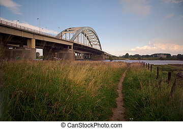 Bridge crossing river Lek with footpath in front