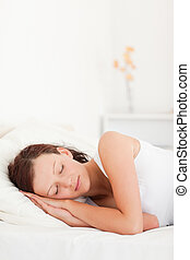 Close up of a sleeping red-haired woman in her bedroom