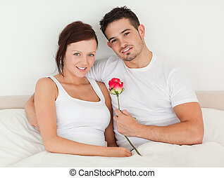Happy couple in a bed with a rose
