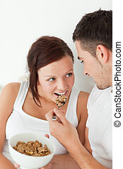 Portrait of a woman fed with cereal by her man