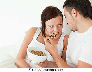 Woman fed with cereal by her man