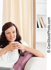 Close up of a woman holding a cup looking at the camera