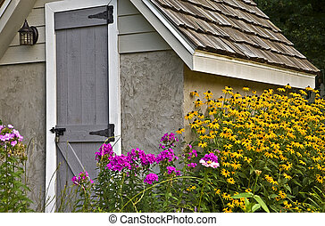 Small Garden Shed with Flowers - A small storage shed in a...