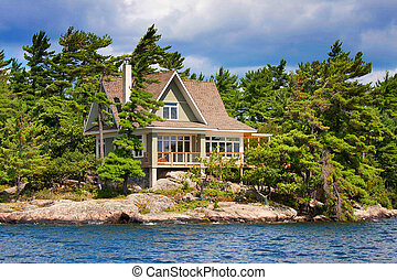 wooden cottage on the lake during summer time