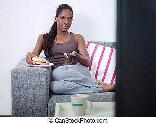 woman eating hamburger and watching tv