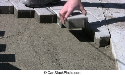 Installing Paving Stones - A worker patiently installs...