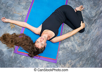 Seen from above, a brown haired caucasian woman doing yoga...