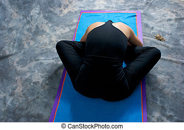 Looking down on an athletic brown haired woman from behind doing yoga exercise Bound Angle Forward Bend pose on yoga mat in studio with mottled background.