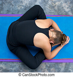Looking down on an athletic brown haired woman doing yoga...