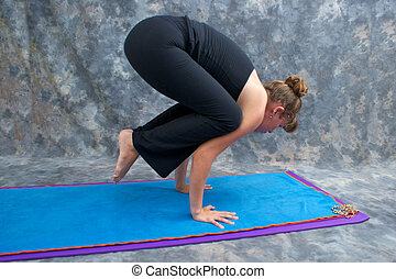 An athletic brown haired woman is balancing in  yoga exercise posture Bakasana or crane crow pose on yoga mat in studio with mottled background.