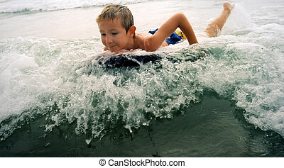 Surfing Boy - Young boy riding the surf on a boogie board