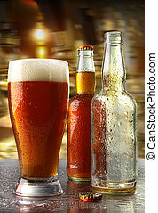 Glass of beer with bottles on counter