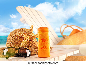 Sunblock lotion and beach items on table - Sunblock lotion...