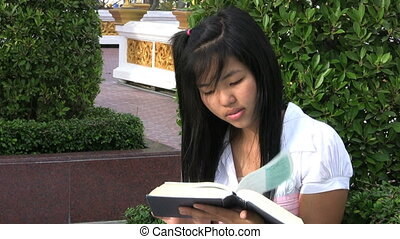 Girl Reading Book Answering Cell - A Thai female university...