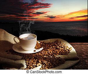 Steaming cup of coffee, cinnamon sticks and a few coffee...