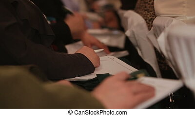 People on the lecture - Person records the information on...