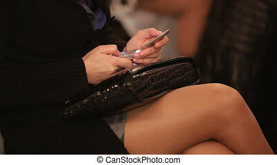 Secret message in a lecture - Woman using mobile phone to...