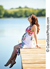 young woman - woman sitting at jetty. summer's day on...