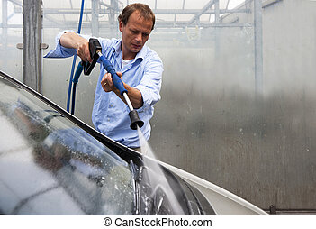 Car wash - Man washing his car in a booth with a high...