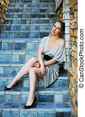 Sad woman on the steps - Thoughtful young woman sitting on...