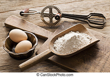 Flour and eggs on wooden background - vintage