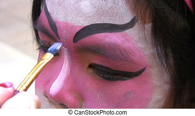Japanese Face Painting-Powder - A beautiful Asian girl sits...