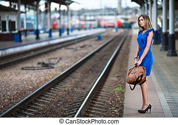 attractive lady waiting train on the platform of railway...
