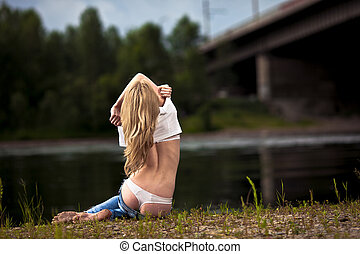 young sexy woman in jeans at the river