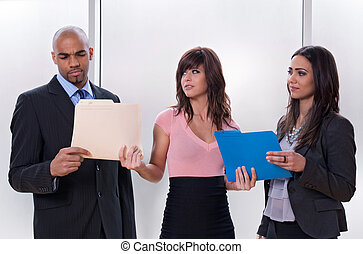 Young woman giving tasks to her colleagues who look...