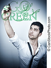 "Go Green - Young business man writing ""go green\"" message..."