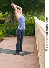 an athletic brown haired woman is doing yoga exercise sun salutation pose outside on a sidewalk in public on an overcast morning.