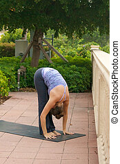 woman doing yoga posture forward fold outdoors in public on mat