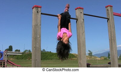 Little Girl On Monkey Bar - A cute little Asian girl shows...