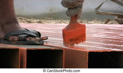 Priming Metal - A couple of migrant workers prime metal on a...