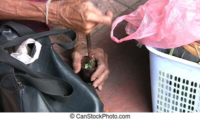Old Asian Lady Grinds Her Tobacco - An old Asian lady uses a...