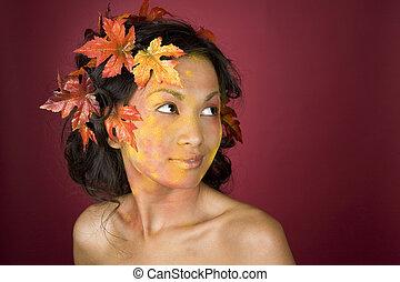 beautiful fall face - pretty brunette woman wearing leaves...