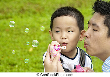 Blowing bubbles - Asian father and son blowing bubbles...