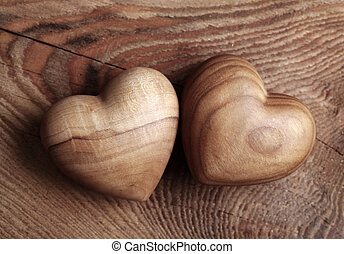 Two wooden hearts on brown background